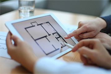 people looking at a floor plan on a tablet